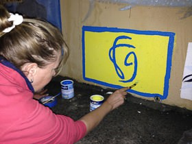 Tracy painting our logo on the wall in Las Palmas