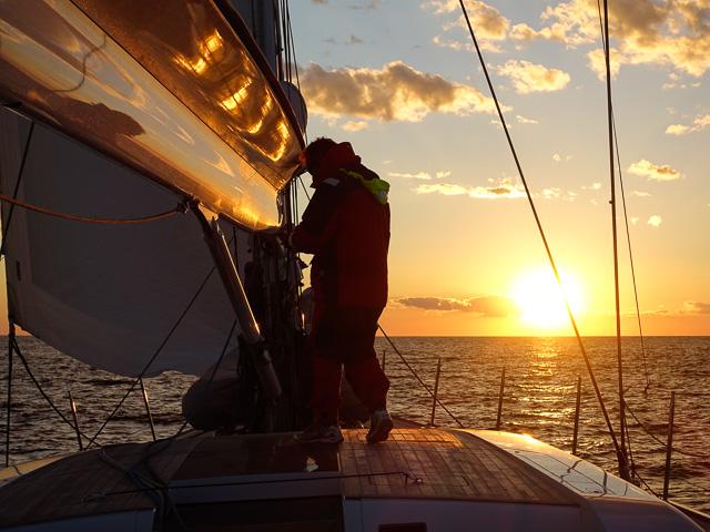 Sail adjustments before nightfall at sea